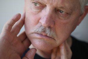 30812079 - senior man touches his sore jaw area